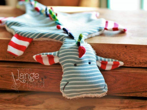 hellblauer Schnullerdrache mit rot-weißen Füßen