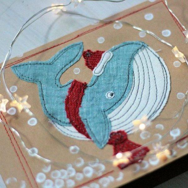 genähter Wal mit Schal und Mütze auf einer Weihnachtskarte aus Kraftpapier