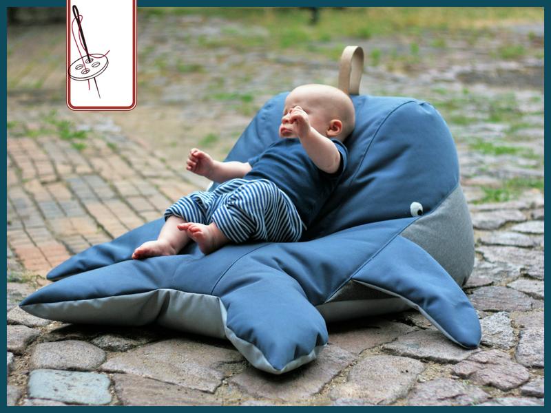 Ein Baby liegt auf einem Sitzsack Wal